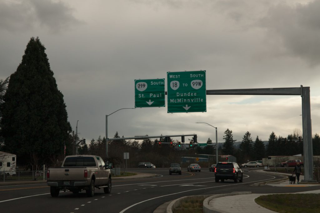"This sign shows where each left turn lane goes. From this perspective, however, it looks like the signs are pointing to the rightmost two lanes, not the leftmost. This sign also says ""OR-18"" instead of ""TO OR-18"", further implicating OR-18 traverses these roads."