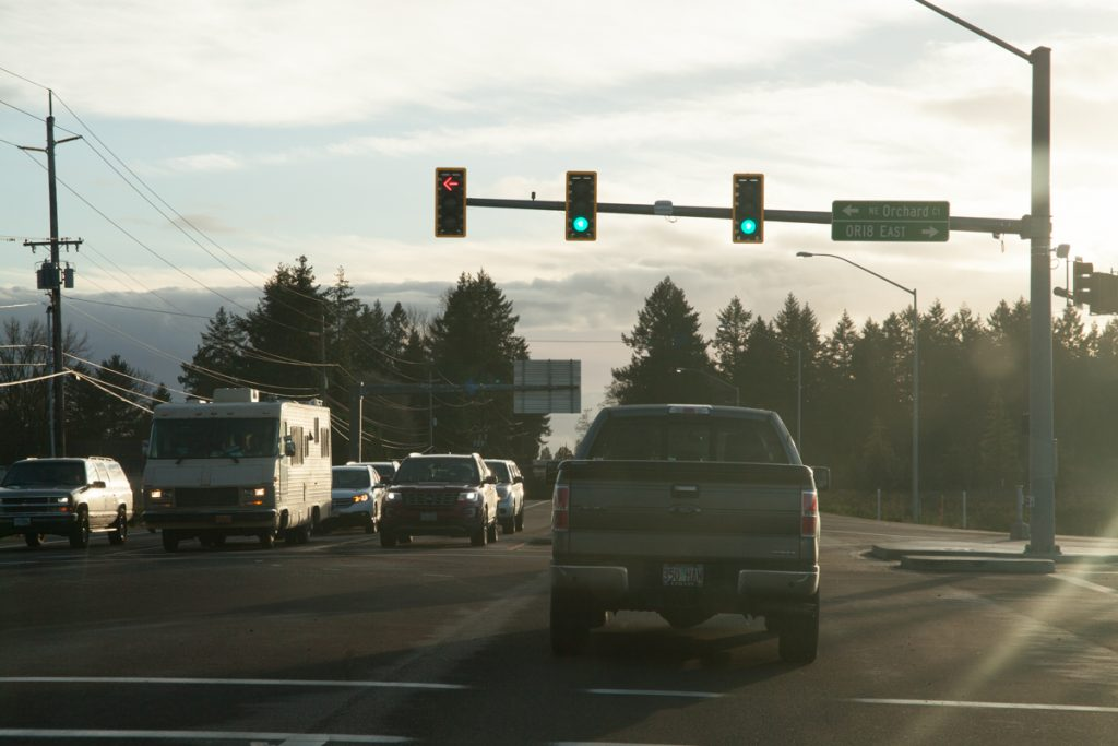 "A green light to head further south. Notice the street sign blade on the traffic light pointing to ""OR18 EAST"", odd considering how rigid ODOT keeps to the shield-in-blade standard as of yet. Size is probably the factor here."